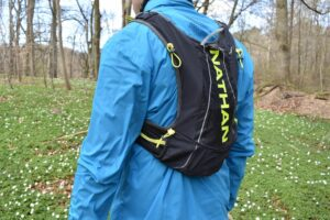 Nathan VaporAir 2.0 Hydration Vest: On the backside the vest has 3 compartments and attachment points for trekking poles (the 4 yellow drawcords)